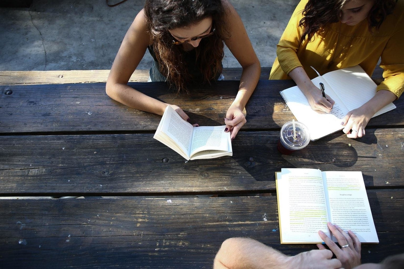 group of people reading and studying together at a table