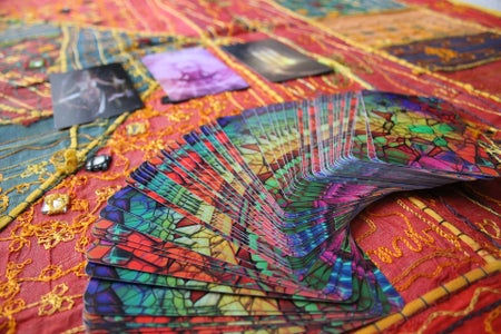 tarot cards spread out over a colorful tablecloth