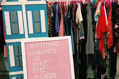 """A pink board that says """"Nothing Haunts us like the things we didn't buy"""" with clothes in the background"""