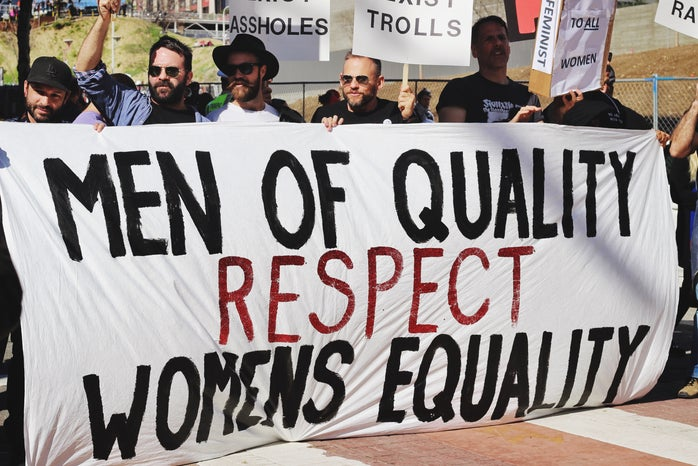 men holding up a banner for women's equality