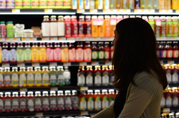 a woman stands in front of the health juice/kombucha shelves at a grocery store