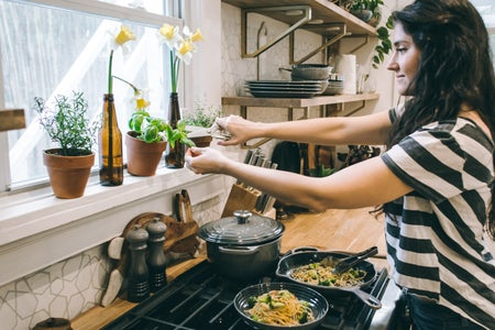 a woman stands over the stove cutting an herb out of a pot on the window sill with a pair of scissors. there are pans of pasta stirfry on the burner.