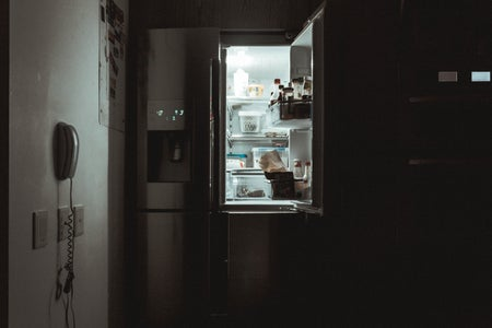 an open fridge door in the darkness