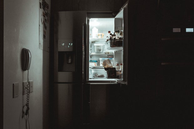 an open fridge door in the darkness
