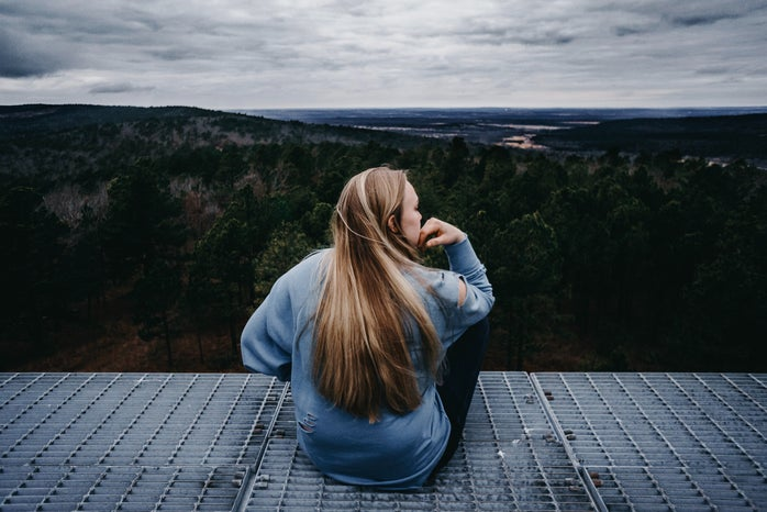 a woman sits on the edge of a deck overlooking the forest