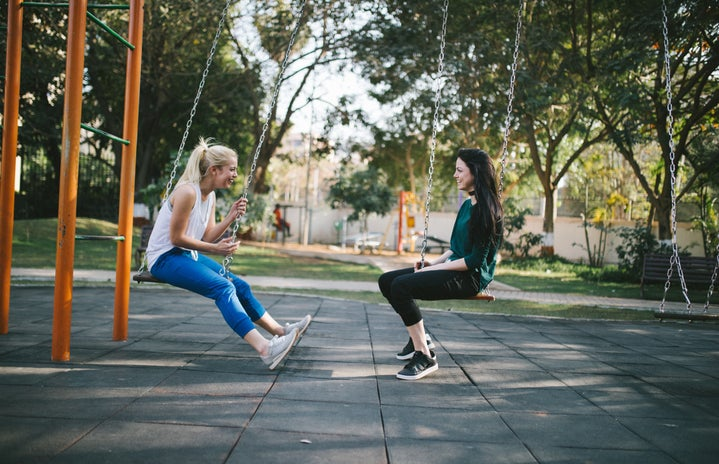 two women sit on a swing set. they are facing each other.