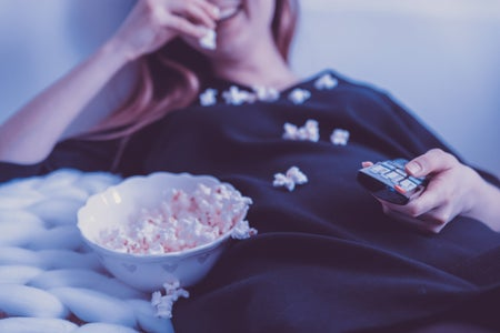 woman lying down eating popcorn