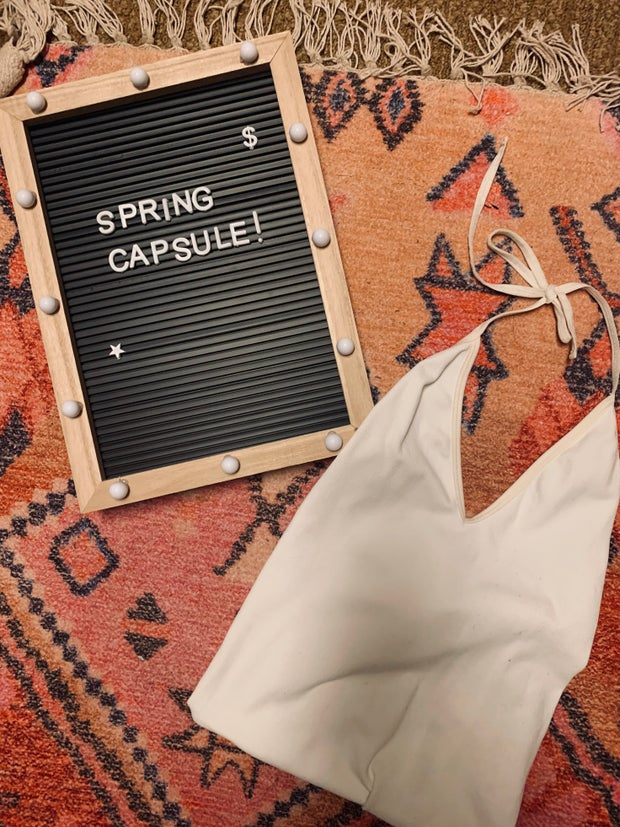 picture of a white bodysuit on a rug next to spring capsule sign