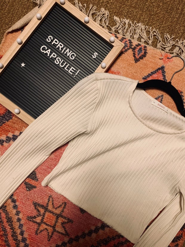 White crop top on a rug next to a spring capsule sign