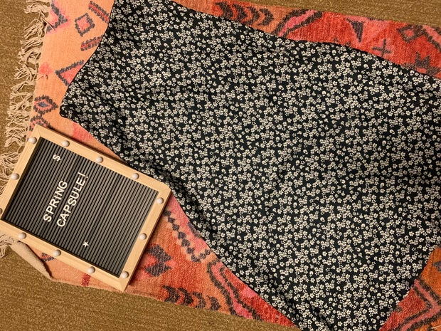 black floral skirt on a rug next to a spring capsule sign