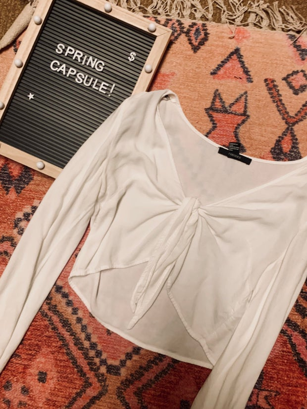 white blouse on a rug next to a spring capsule sign