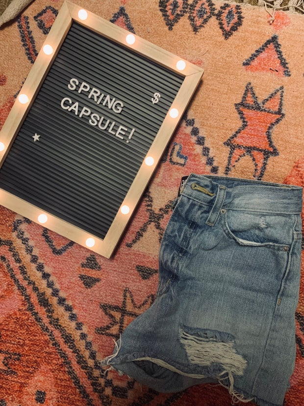 demin shorts on a rug next to a spring capsule sign