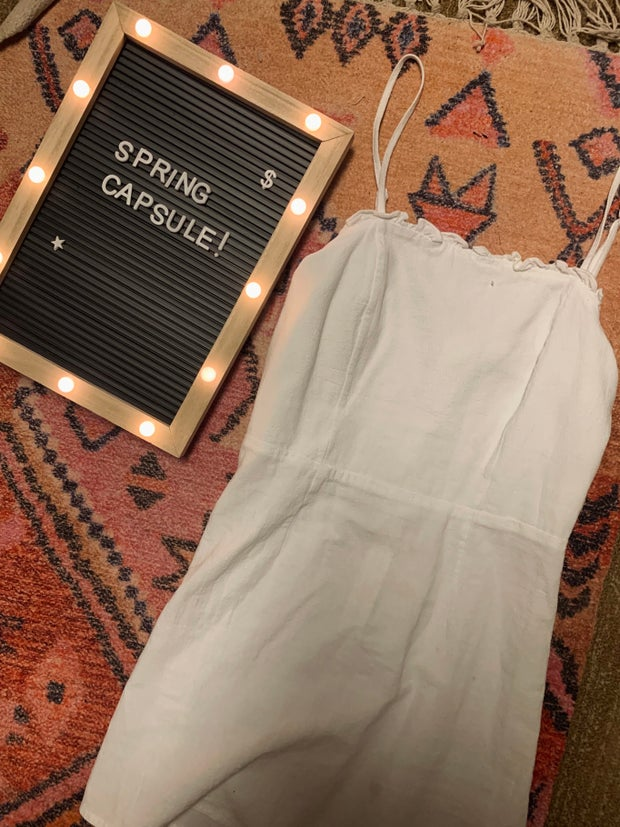 white dress on a rug next to a spring capsule sign