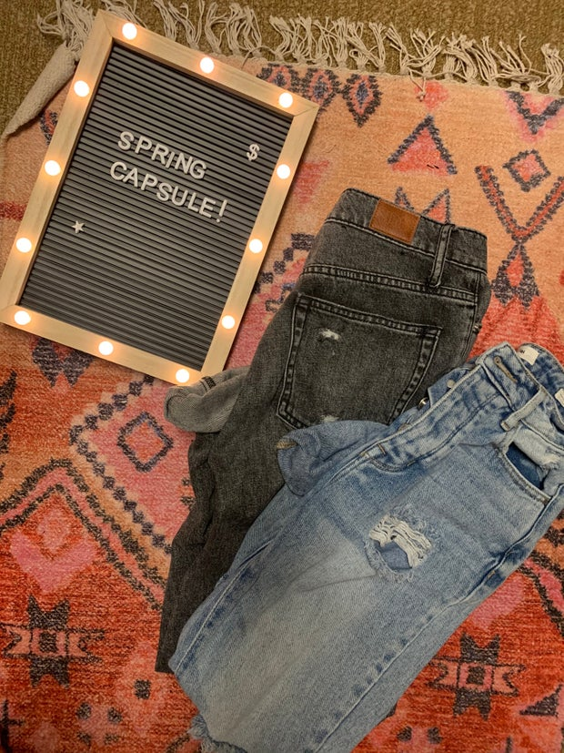 jeans on a rug next to a spring capsule sign