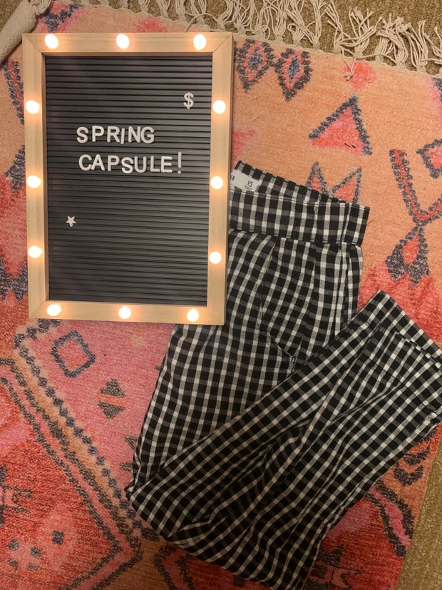 gingham pants on a rug next to a spring capsule sign