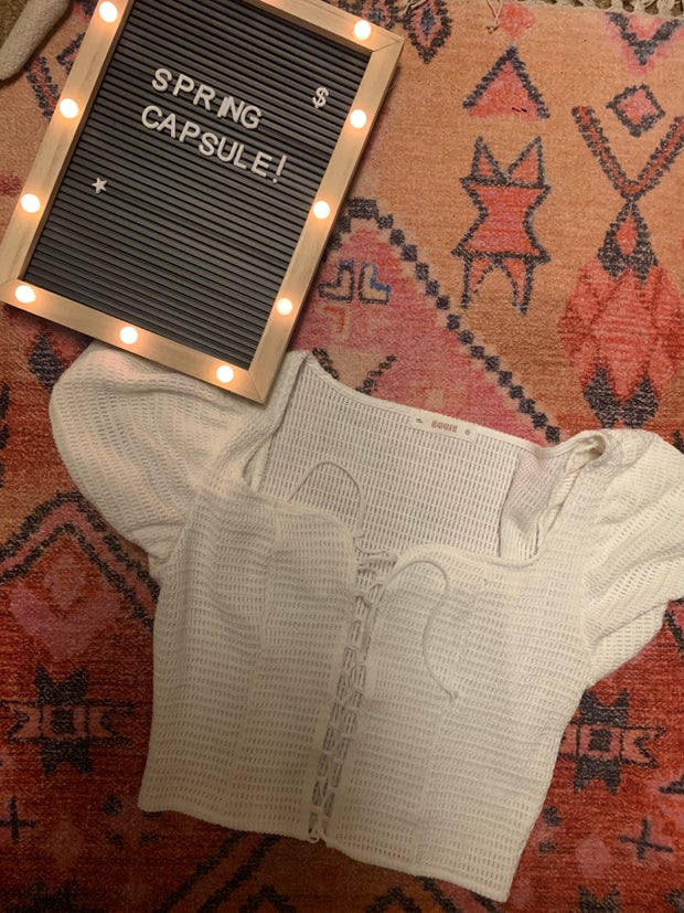 white lace up blouse on a rug next to a spring capsule sign