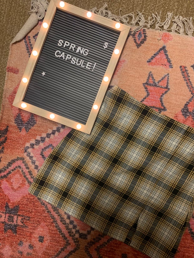 plaid skirt on a rug next to a spring capsule sign