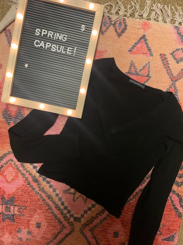 black long sleeve on a rug next to a spring capsule sign