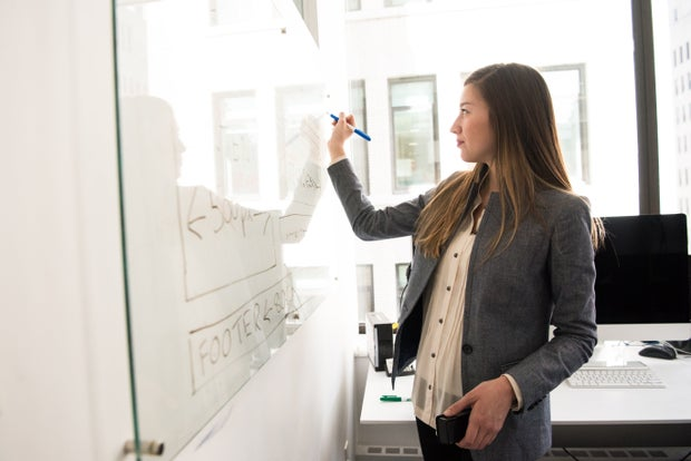 a woman in business casual stands in front of a white board, writing with a marker in an office space