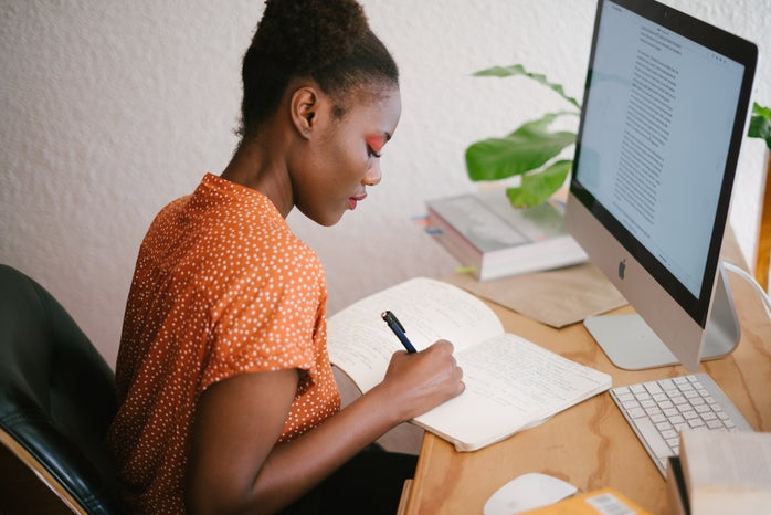 a woman sits at a wooden desk writing in a notebook. there is an imac in front of her.