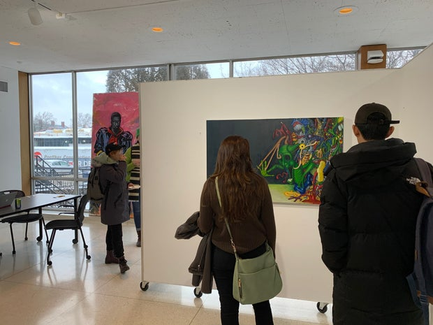 People viewing and walking around an exhibition/gallery.