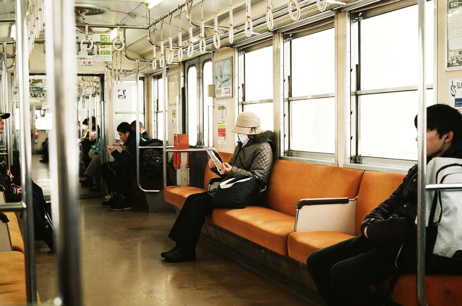 Masked person sitting on subway train car
