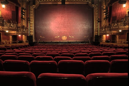 An ornate theatre with red chairs and stage curtain.