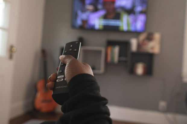 Hand holding remote pointed at tv screen