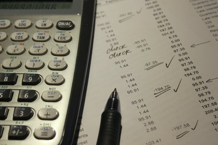 a calculator covers a spreadsheet of expenses
