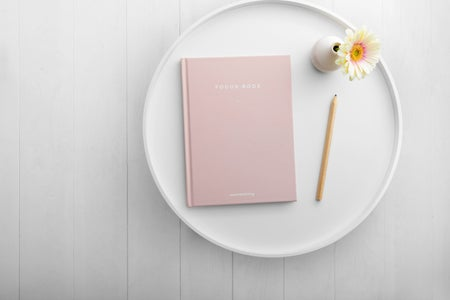 pink notebook on white dish
