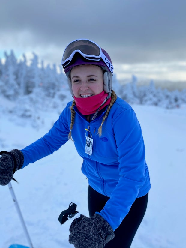 girl in blue jacket and skis smiling