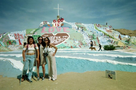 3 girls in front of salvation mountain