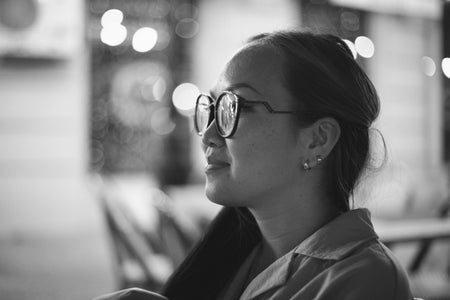 Black and white photo of an Asian woman with a black-framed eyeglasses