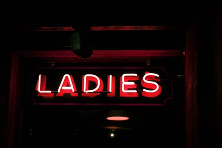 Red neon light singnage that says 'ladies'