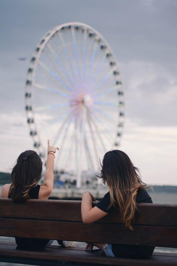 Girls on bench in front of ferris wheel