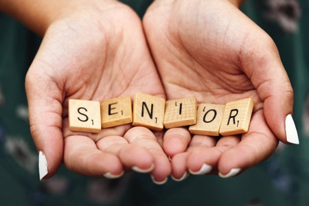 A girl with white nail polish holding scrabble letters spelling the word SENIOR