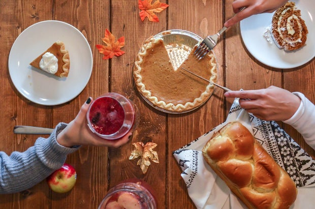 wooden dinner table with pie, bread, and cake