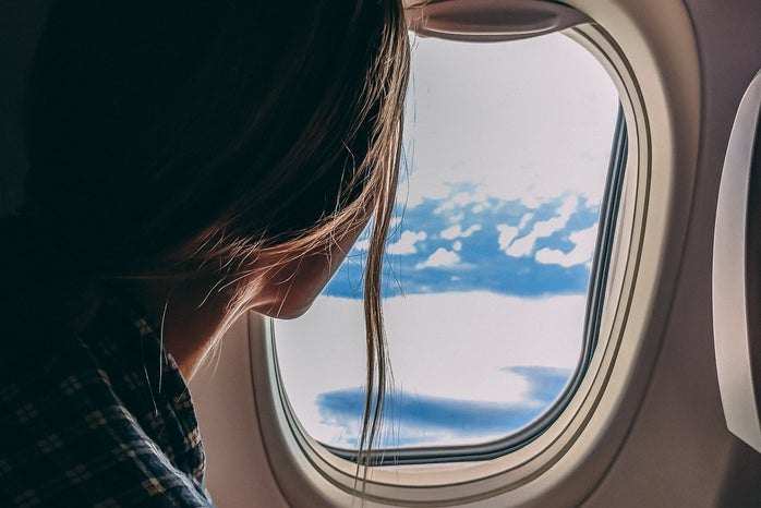 person looking out airplane window