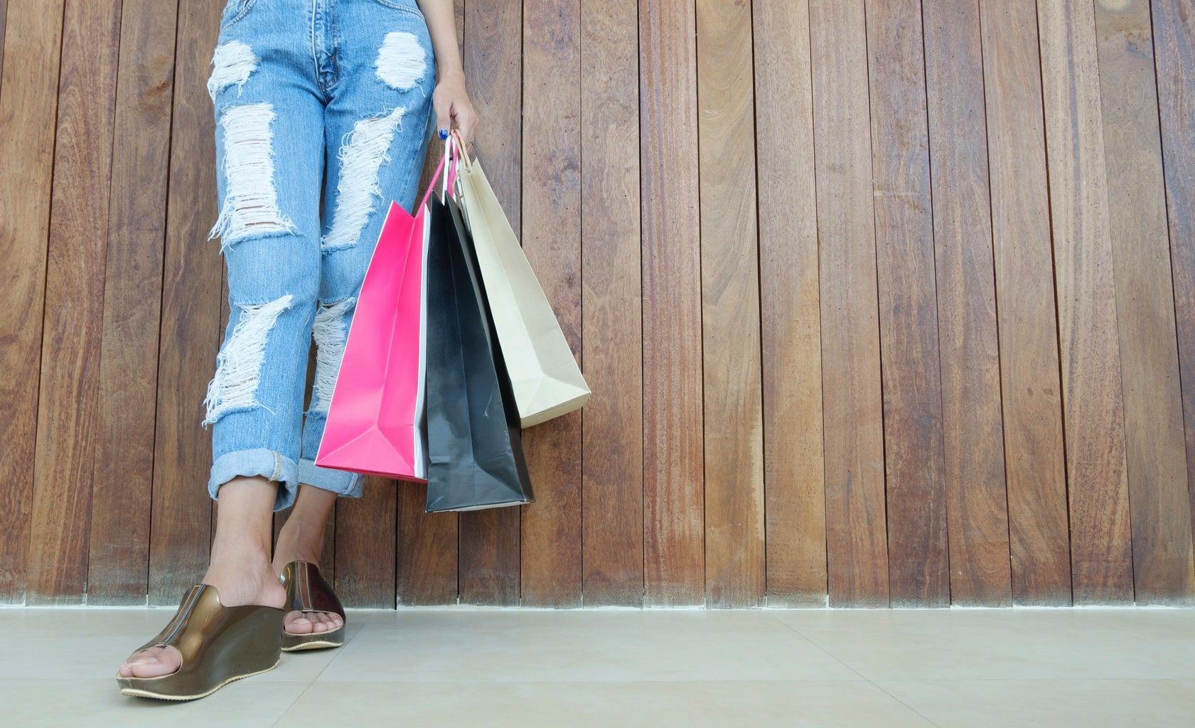 Girl\'s feet with distressed jeans and shopping bags