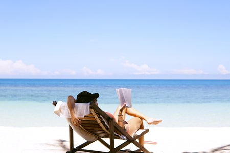 Woman on a wooden chair reading at the beach