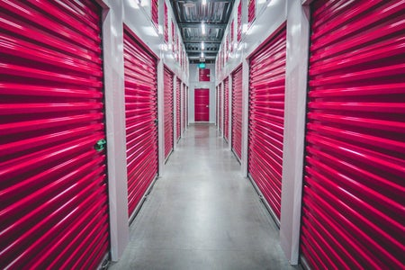 a hallway in a storage facility with purple rolling doors lining each side.
