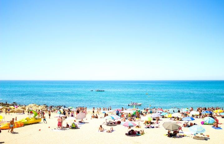 crowd on beach under blue sky Oliveira
