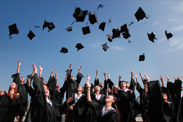 Newly Graduated People Wearing Black Academy Gowns Throwing Hats Up in the Air
