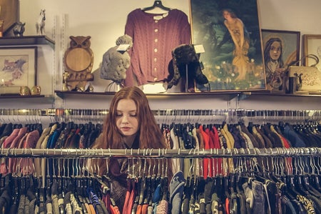 Young girl shopping and looking at a clothes rack