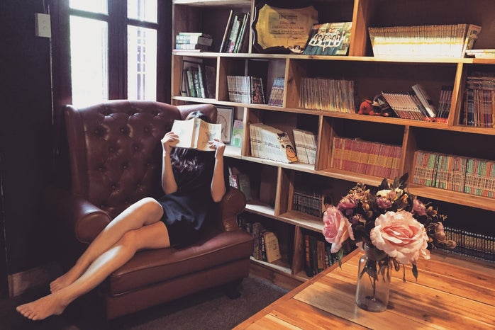 Woman hiding her face with a book in a library wearing a dress