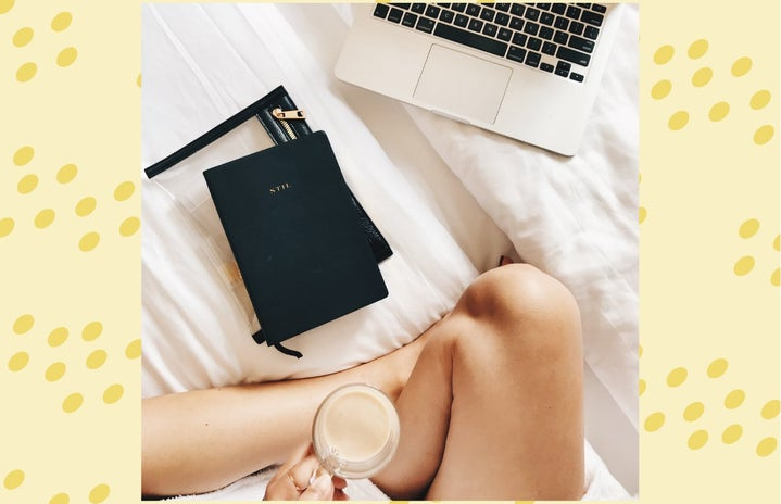 person holding coffee cup working from bed