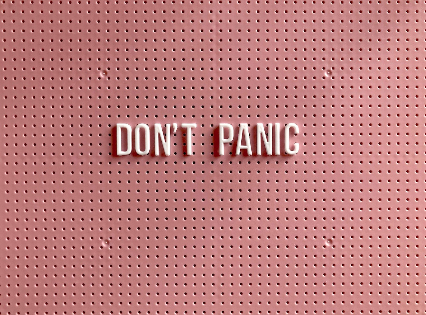 Don\'t Panic sign with pink backdrop