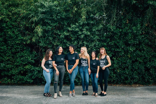 a group of women wearing shirts that say