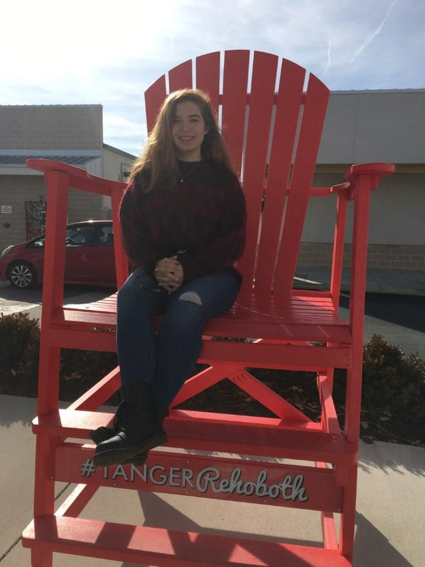 woman sitting in big red beach chair