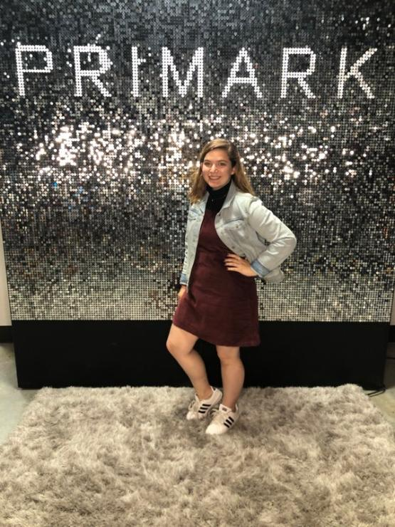 woman posing in front of Primark fashion sign